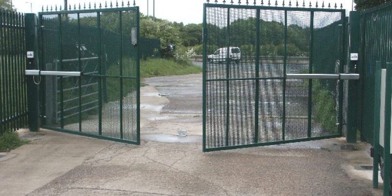 Large industrial steel gate painted in green colour which is operates automatically when the vehicles comes in or goes out.